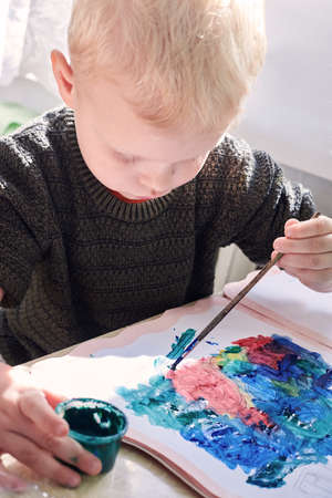 A three-year-old boy paints with gouache coloring, leisure and child development.