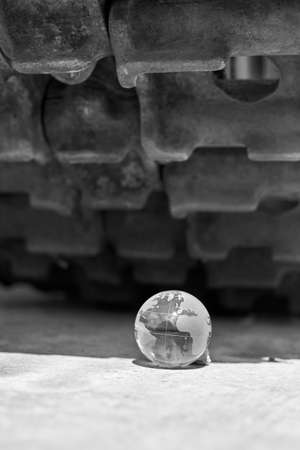 The glass globe of planet Earth under the tracks of the tank, the concept of war, black and white photo.