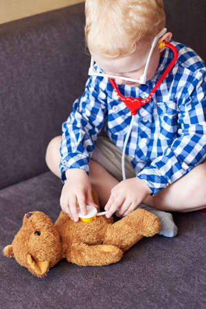 Little boy playing doctor with toy tools and teddy bear at home.