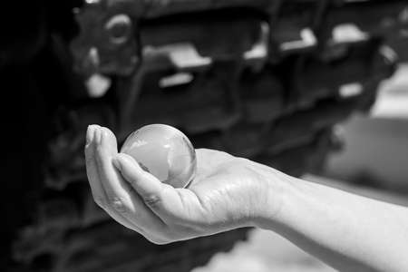 The glass globe of planet Earth in a woman's hand under the tracks of the tank, the concept of war, black and white photo. Banco de Imagens