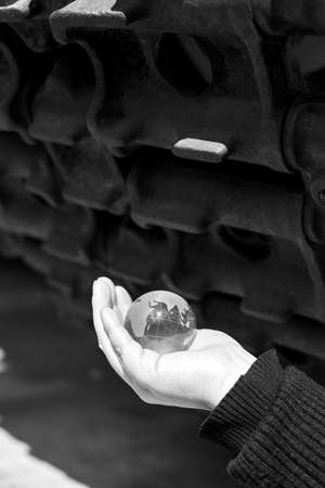 The glass globe of planet Earth in a woman's hand under the tracks of the tank, the concept of war, black and white photo.