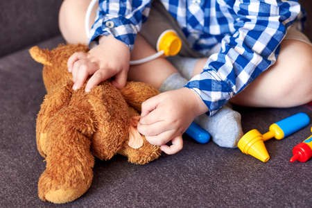 A little boy glues a plaster on a teddy bear, playing doctor, close-up. Banco de Imagens