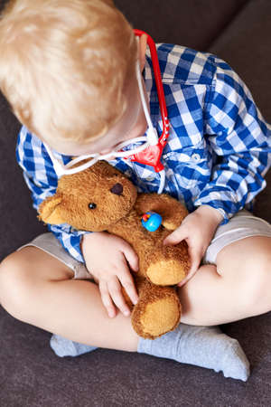 A little boy measures the temperature of a teddy bear with a toy thermometer, children's games. Banco de Imagens