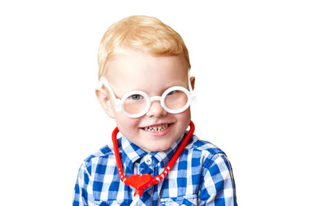 Portrait of a funny three year old boy wearing toy glasses with a stethoscope, isolated on white background.