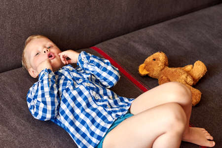 A three-year-old boy with mental disabilities lies on the couch near the teddy bear at home. Banco de Imagens