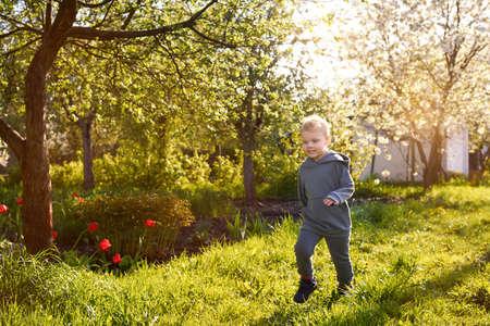 A three-year-old joyful boy runs on the grass in a blooming garden in spring. Banco de Imagens