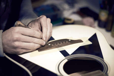 A service worker repairs a guitar with a tool, toned photo. Banco de Imagens