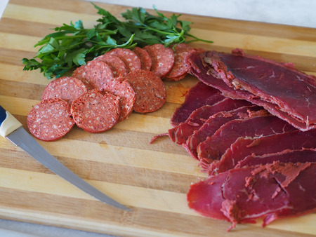 sliced turkish sausage and bacon on cutting board. Knife, sausage and bacon on wood Stock Photo