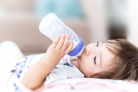 a baby drinking milk or follow-on milk with a bottle