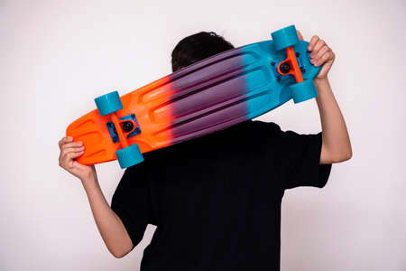 young boy holding colorful skateboard in hand and white background