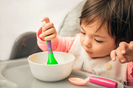 Child trying to eat food with spoon in baby highchair. eating training on chair