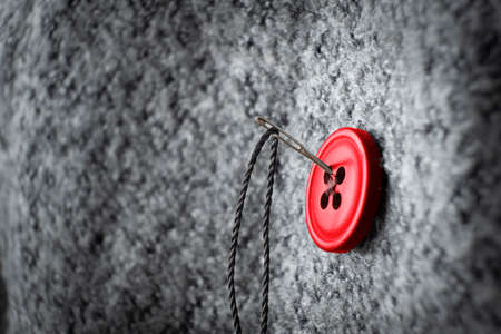 button on thick coat fabric and thread with needle on it