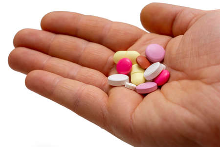 tablet medicines in many different colors in the palm