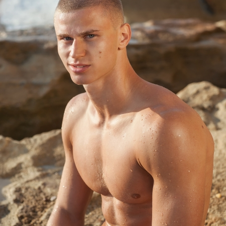 Sexy young handsome muscular man sit at the big rock on the beach  In sunshine at sunset   photo