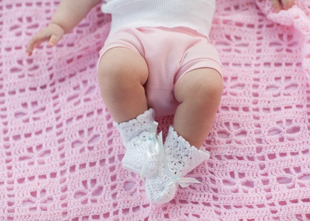 Baby feet in motion. Newborn lying on a pink blanket. photo