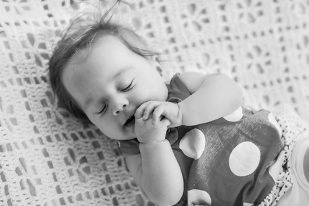 Black and white photo  Sweet little baby sleeping  She in blue dress with white polka dots  photo