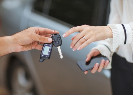 Male hand giving car key to female hand  She is holding a cell phone  In the background, a fragment of the car