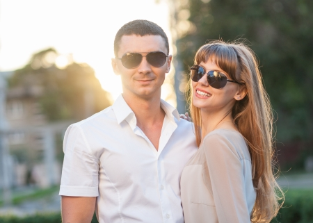 Young couple in love outdoor  They re wearing sunglasses  In the background, the rays of the setting sun  photo