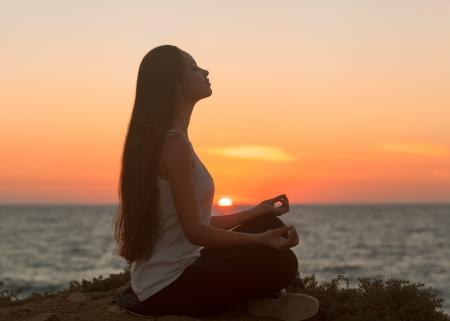 Girl in lotus pose at sunset Asian Caucasian female model