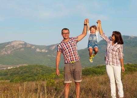 gente saludable: Feliz madre, padre e hija en la puesta del sol