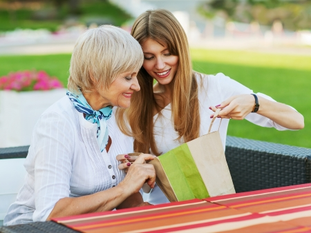 Adult mother and daughter are considering buying after shopping  They are sitting in a cafe outside  photo