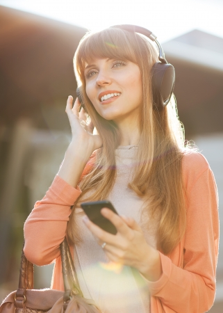 Young beautiful hipster girl listening to MP3 player on the street photo