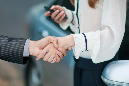 business transaction: Business transaction, she shakes hands with a man buying a car Stock Photo