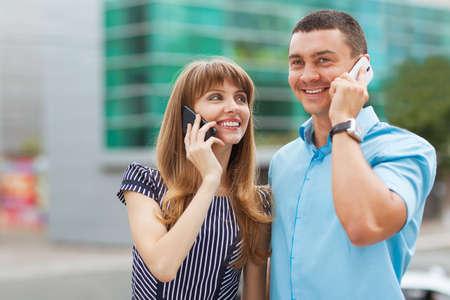 Stylishly dressed young couple talking on the phone  photo