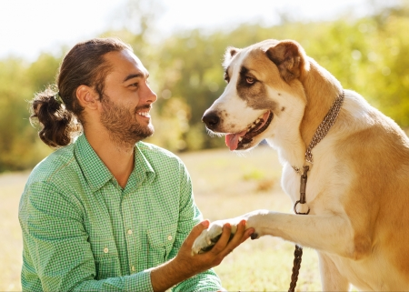 Man en Centraal-Aziatische herder in park Hij houdt een hond