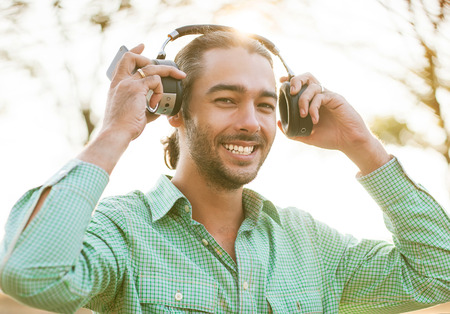 hipster young man listening to music on the street, takes headphones and smiling at the camera. photo