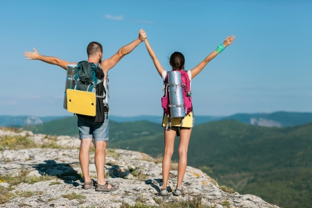 two tourists stand on the mountain and raise your hands up photo