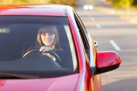 woman driving car: girl traveling by car smiling