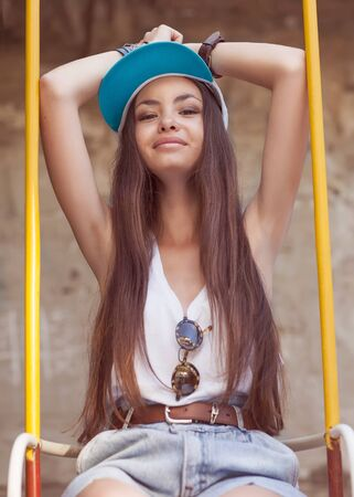 hipster girl sitting on a swing photo
