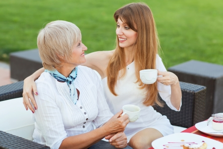 adult mother and daughter drinking tea or coffee and talking outdoors photo
