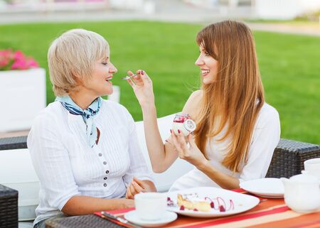 Senior mother and young attractive daughter eating cake, drinking coffee at coffee shop, smiling photo