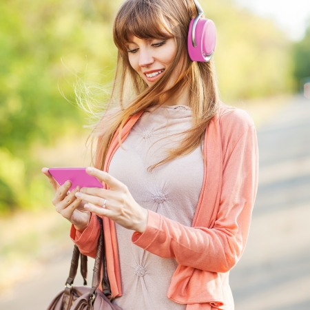 Young beautiful girl listening to MP3 player on the street  photo