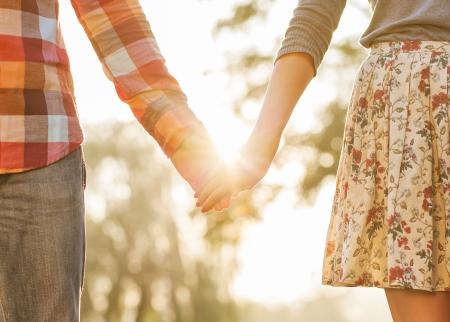 femme romantique: Jeune couple amoureux de marche dans le parc en automne tenant par la main en regardant dans le coucher du soleil