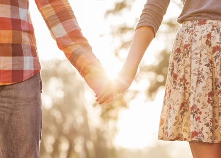 emotional woman: Young couple in love walking in the autumn park holding hands looking in the sunset