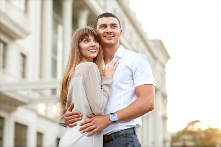 he and she: Young couple in love outdoor. She pressed against him, he is a gentle hugs her.