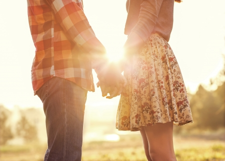 恋夕日に手を繋いでいる秋の公園で歩く若いカップル