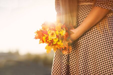 A young girl in a checkered dress with a bouquet in the sunshine  photo