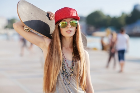 Portrait of a girl with a skateboard in her hand, outdoors Stock Photo