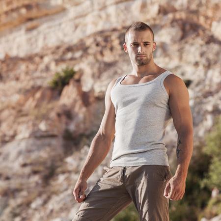 Fashion portrait of a muscular toned male model on beautiful beach in bikini swim trunks photo
