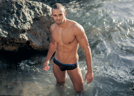 Portrait of a handsome young muscular man in swimtrunks with water ocean background photo