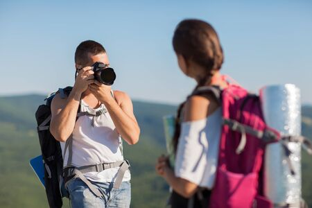 Two tourists  Man photographs woman, she is holding a map  photo