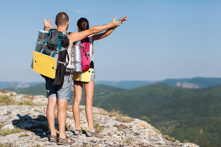 Hikers with backpacks enjoying valley view from top of a mountain  The concept of freedom  photo