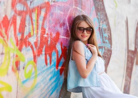 hipster girl outdoors stands near a graffiti wall photo