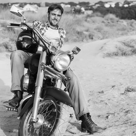 Biker man sits on a retro bike photo