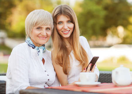 mature old generation: adult mother and daughter drinking tea or coffee and talking outdoors