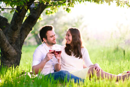 a man and a woman in the park  sit on the grass and drink wine  photo